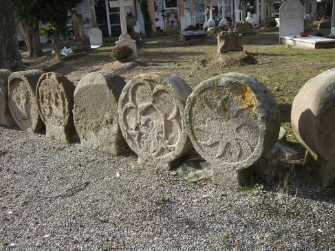 20.08.2007 Fragment de la sèrie de les gairebé 70 esteles funeràries visibles al cementiri de Sanaüja. Tot i estar en una fase de degradació galopant, a l'estar exposades a l'intempèrie, encara predomina la seva més o menys fàcil identificació. En la que veiem en primer terme podem observar una roda solar. El conjunt d'esteles és datable en el periode comprés des del s. XIII al XIX, amb una abundant representació de les èpoques medievals.         Sanaüja. Cementiri -  Jordi Bibià