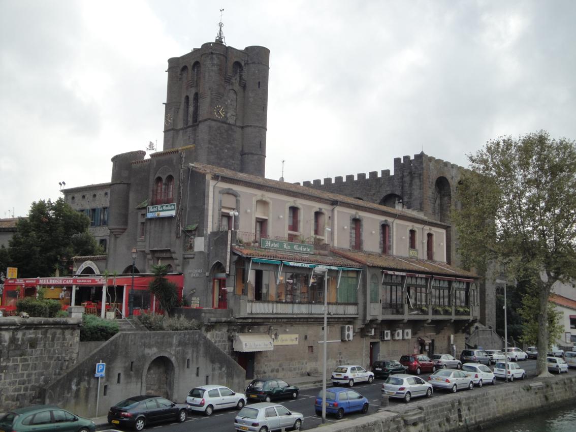 06.10.2009 Altra imatge des de l'Érol, on un cop més destaca la seva imponent torre-campanar de 35 m d'alçada del s. XIII, una torre ben be castellera. L'edifici annex —el qual presenta una façana clara— i que està edificat paral·lelament al riu, fou bastit en el s. XII amb funció residencial pels bisbes, funció que estigué en vigor fins el 1760. Ara forma part de les instal·lacions de l'hotel de la <em>Galiote</em>.                                                       -  Jordi Bibià